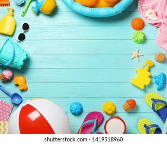 Flat lay composition with beach toys on color wooden background. Space for text