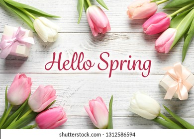 Flat lay composition of beautiful flowers and text Hello Spring on light wooden background
