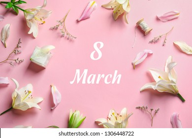 Flat lay composition with beautiful lily flowers and text 8 March on pink background. International Woman's day