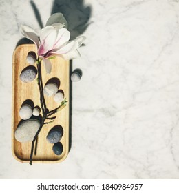 Flat lay composition with beautiful spring magnolia flowers and grey stones on white marble background. Relaxation and zen like concept.