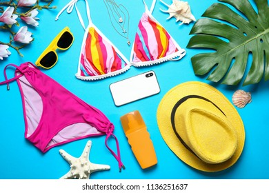 Flat lay composition with bikini, smartphone and beach objects on color background