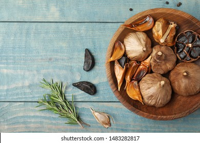 Flat lay composition with black garlic on blue wooden table. Space for text