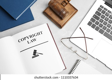 Flat lay composition with book, gavel and laptop on grey background. Copyright law concept