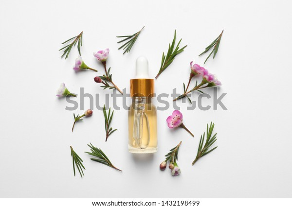 Flat lay composition with bottle of natural tea tree oil on white background