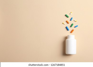 Flat lay composition with bottle, pills and space for text on color background