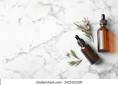 Flat lay composition with bottles of natural tea tree oil on marble table, space for text