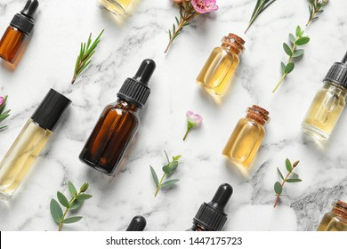 Flat lay composition with bottles of natural tea tree oil on white marble background