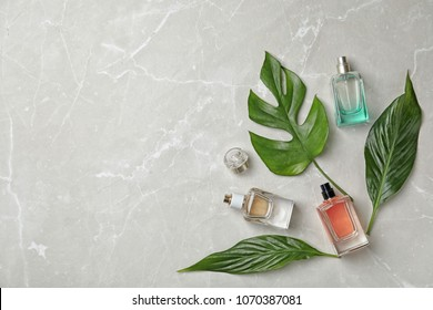 Flat lay composition with bottles of perfume on grey background