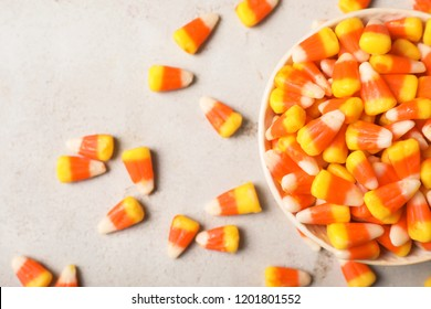 Flat lay composition with bowl of delicious candy corns on gray background