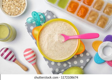 Flat lay composition with bowl of healthy baby food on white background