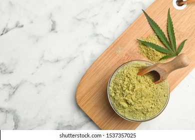 Flat lay composition with bowl of hemp protein powder on marble table. Space for text