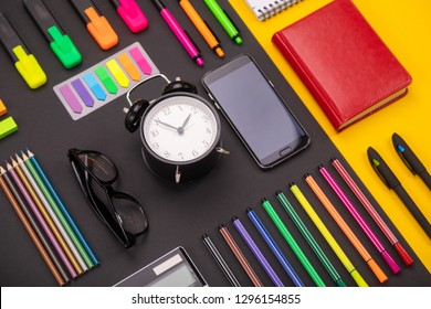 Flat lay composition of business desk with alarm clock, smartphone, notebook, stickers, and colored pens on colorful black and yellow background