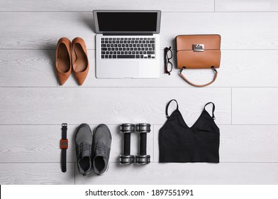 Flat lay composition with business supplies and sport equipment on white wooden floor. Concept of balance between work and life