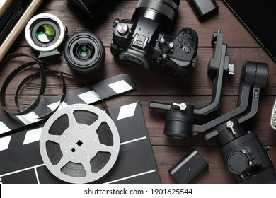 Flat lay composition with camera and video production equipment on brown wooden background