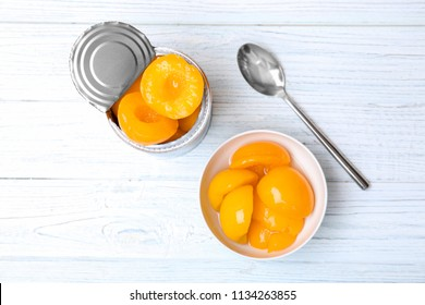 Flat lay composition with canned peaches on wooden background