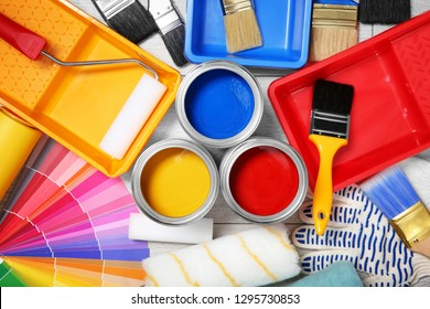 Flat lay composition with cans of paint and decorator tools on wooden background