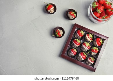 Flat lay composition with chocolate covered strawberries on grey background