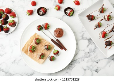 Flat lay composition with chocolate covered strawberries on marble background