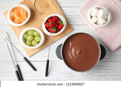 Flat lay composition with chocolate fondue in pot and fruits on wooden background