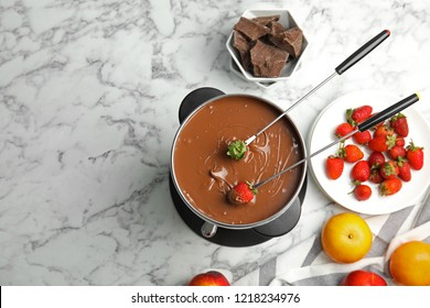Flat lay composition with chocolate fondue in pot and space for text on marble background