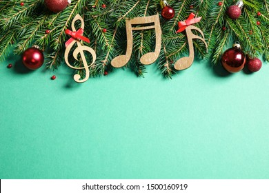 Flat lay composition with Christmas decor and music notes on light green background, space for text