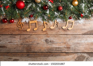 Flat lay composition with Christmas decor and music notes on wooden table, space for text