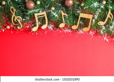 Flat lay composition with Christmas decor and music notes on red background, space for text