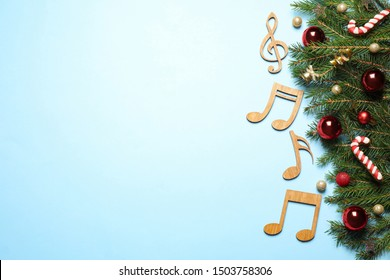 Flat lay composition with Christmas decor and music notes on light blue background, space for text