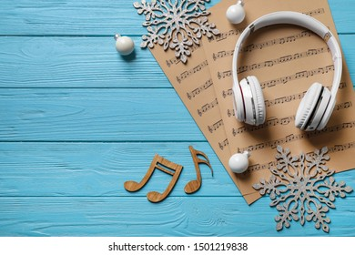 Flat lay composition with Christmas decorations, headphones and music sheets on blue wooden table, space for text