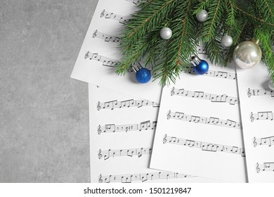 Flat lay composition with Christmas decorations and music sheets on table. Space for text