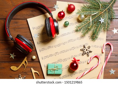 Flat lay composition with Christmas decorations, headphones and music sheets on wooden table