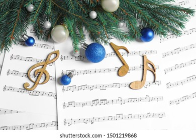Flat lay composition with Christmas decorations and wooden music notes on sheets