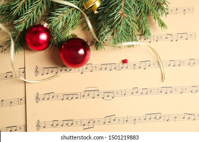Flat lay composition with Christmas decorations on music sheets