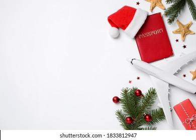 Flat lay composition with Christmas decorations, toy airplane and passport on white background, space for text. Winter vacation