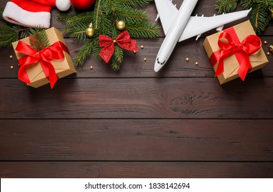 Flat lay composition with Christmas decorations and toy airplane on wooden background, space for text. Winter vacation