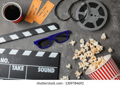 Flat lay composition with clapper and popcorn on grey background. Cinema snack