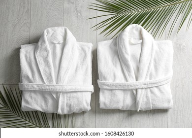 Flat lay composition with clean folded bathrobes on light wooden background