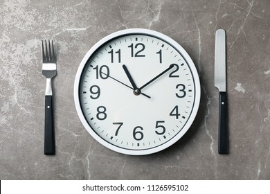 Flat lay composition with clock and utensils on grey background. Time management