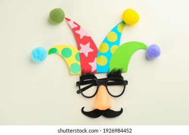 Flat lay composition with clown's face made of party glasses and hat on white background