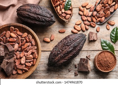 Flat lay composition with cocoa beans, chocolate pieces and pods on wooden table