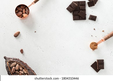 Flat lay composition with cocoa beans, chocolate pieces, cocoa powder and pods on white concrete background. Organic food, natural chocolate. Top view, copy space for text.