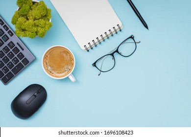 Flat lay composition with coffee, keyboard, empty paper notepad and other office related objects ob blue background