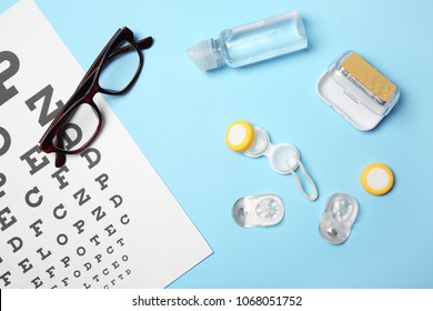 Flat lay composition with contact lenses, glasses and accessories on color background