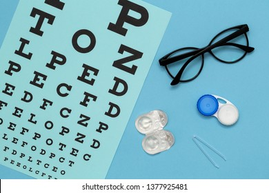 Flat lay composition with contact lenses, glasses and accessories on blue background. Vision concept.