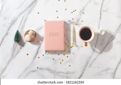 Flat lay composition with coral colored 2021 diary book for writing down New Year's plans, coffee, cookie and mini artificial Christmas trees onside with gold sparkles on white background. Holiday