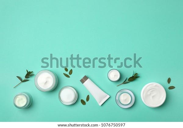 色の背景に化粧品を含むフラットレイ組成物