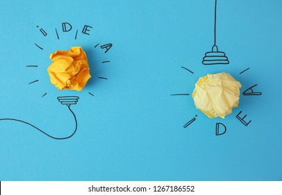 Flat lay composition with crumpled paper as lamp bulbs and words IDEA on color background