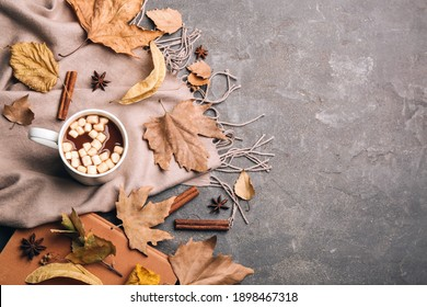 Flat lay composition with cup of hot drink and autumn leaves on grey table, space for text. Cozy atmosphere