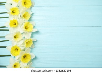 Flat lay composition with daffodils and space for text on wooden background. Fresh spring flowers