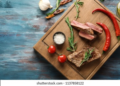 Flat lay composition with delicious grilled meat, rosemary and vegetables on wooden background